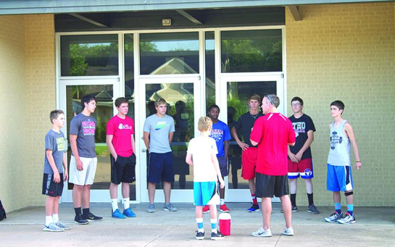 From left, Evan Ranger, Hayden Husen, Marcus Brooks, Garrett Gatlin, Marc Tate, Austin Bahl, Jake Holland and Sam Perkins listened while coach Marcus Morris stood next to his son, Conrad, and talked to his runners about running safely before cross country training began Monday.