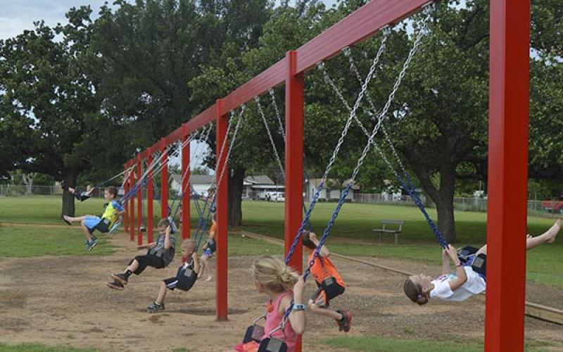 Kids at Crestview Elementary swing on 16 sets of swings recently added to the playground. The project was funded by the school's PTO.