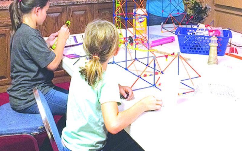 Pictured from left to right are Lizzy Tenut, Hannah Tenut and Abby Tenut who are constructing a rollercoaster from K'NEX as part of the Graham Robotics Academy program. Courtesy photo