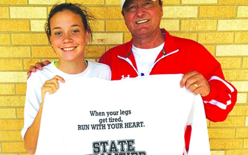 Graham Lady Blues varsity cross country runner Khloe Morris poses alongside Lady Blues head coach Ky Graham with a state qualifier shirt after Morris finished 12th this past Saturday at the regional cross country meet giving her a chance to run on Nov. 12 at Old Settlers Park in Round Rock at the state meet. Courtesy Photo
