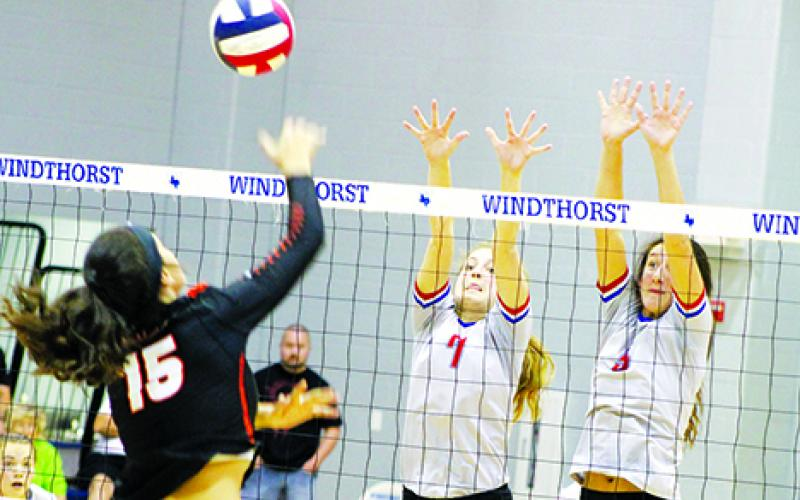 Graham Lady Blues players Baylee Loomis, left, and Jasmine Sims jump up at the net for an attempted double block on a Burkburnett Lady Bulldog during the first set of the district tiebreaker game Friday afternoon from Windthorst High School. Leader photo by Evan Grice