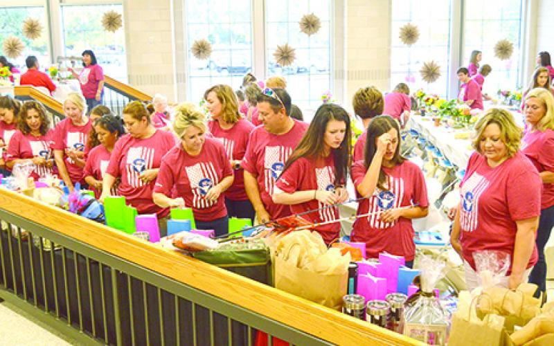 GISD teachers and educators place raffle tickets into bags which were given as prizes in a drawing at the GISD Back to School Staff Breakfast in the Graham High School lunchroom.