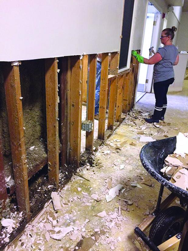 Melissa Croxton, part of a group from Oak Street Baptist Church in Graham, is shown removing sheetrock at Of the Way Bible Church in Baton Rouge. Courtesy photos