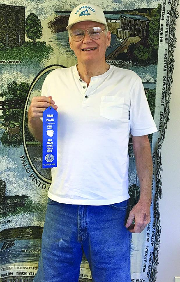Shown is Wayne Cobb of Graford, with the first place ribbon that he won with his Schley variety pecans at the Texas State Pecan Show.  (Courtesy photo/Texas Agrilife Extension Service)