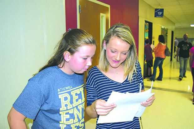 Claire Adams and Aubrey Johnston compare their seventh grade schedules at Graham Junior High during Meet the Teacher events held Thursday afternoon and evening at Graham ISD schools.