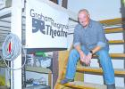 Graham Regional Theatre Managing Director Christian Sanders sits on the steps in the back room of 'The Perry' downtown theater. Sanders was hired to work full time this season to work on new shows and events for GRT.