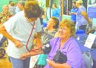 Roxie Durham, a home health aide from Young County Home Health, checks Joan Blakenship's blood pressure at the annual Graham Community Health and Wellness Fair presented by Graham Regional Medical Center.