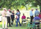 Robyn Fontenot shakes hands with retired Texas Ranger Phil Ryan, while retired Ranger Dick Johnson, left, looks on, during the gathering before the dedication of a special Ranger Memorial Cross at the grave of Fontenot's ancestor, Charles Lemuel Ray. Between Fontenot and Ryan is Kay Dosher, whose genealogical research led to the discovery that Ray and his brother both were rangers in 1874-75.