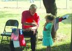 Orville Dunsworth, of Oklahoma City, hands a hawk feather to Lacie Dosher, 4, prior to a dedication ceremony of a Texas Ranger Memorial Cross at the grave of their ancestor, Charles Lemuel Ray, at Farmer's Cemetery in northern Young County.